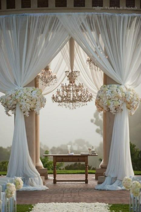 Draped outdoor ceremony spot with chandliers